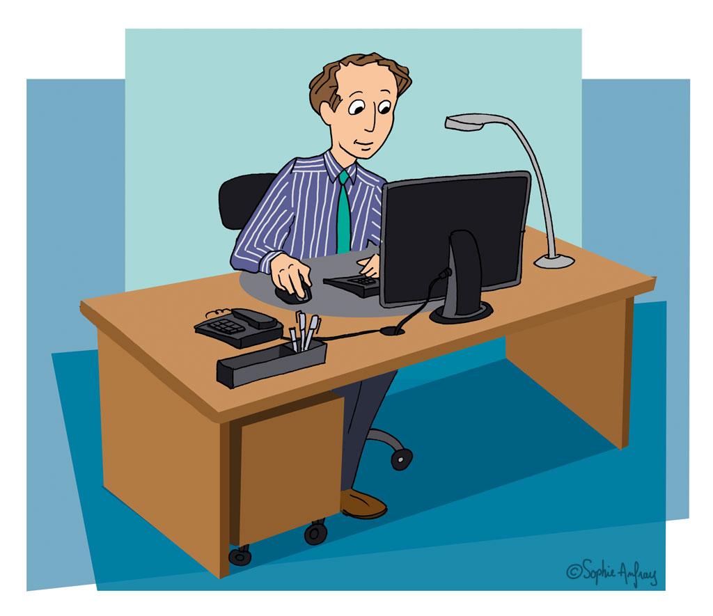 Un homme assis à son bureau derrière son ordinateur.
