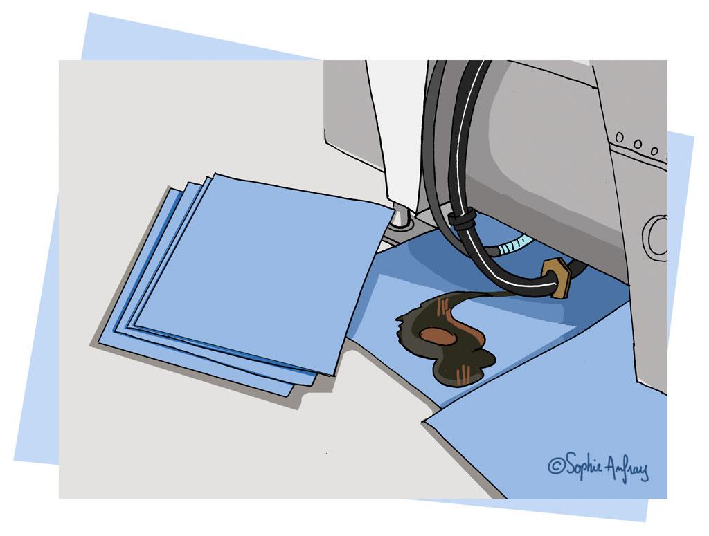 Fuite d'hydrocarbure stoppée par un papier absorbant pour prévenir la pollution.